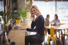 Portret van het glimlachen het blonde vrouw spreken op mobiele telefoon terwijl het gebruiken van laptop Stock Fotografie