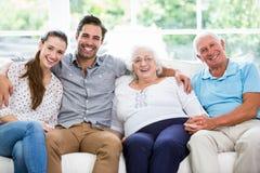 Portret van het glimlachen de familiezitting van meerdere generaties op bank Royalty-vrije Stock Afbeeldingen
