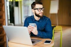 Portret van het glimlachen het bericht van de bedrijfsmensenlezing met smartphone in bureau Stock Foto's