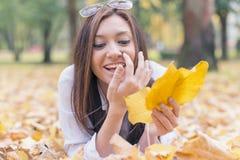 Portret van het glimlachen het jonge vrouw liggen op de herfstbladeren royalty-vrije stock foto's