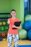 Portret van het glimlachen het vrouwelijke geschiktheidsinstructeur schrijven in klembord terwijl status in gymnastiek Stock Fotografie