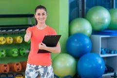 Portret van het glimlachen het vrouwelijke geschiktheidsinstructeur schrijven in klembord terwijl status in gymnastiek Royalty-vrije Stock Afbeelding