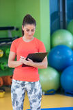 Portret van het glimlachen het vrouwelijke geschiktheidsinstructeur schrijven in klembord terwijl status in gymnastiek Stock Foto