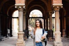 Portret van het glimlachen het vrouwelijke student tonen o.k. in openlucht dichtbij Universiteit Stock Foto