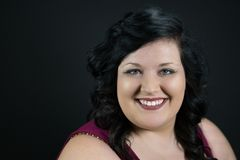 Portret van het glimlachen jong vrouwelijk model met donker haar, eerlijke huid en rode lippen Stock Foto