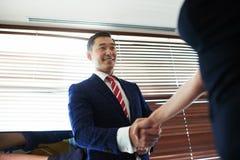 Portret van het glimlachen jonge het leiden directeur het schudden handen met zijn partners terwijl status in bureau ruimtebinnen Royalty-vrije Stock Fotografie