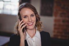 Portret van het glimlachen het jonge mooie vrouwelijke redacteur spreken op cellphone Stock Afbeeldingen