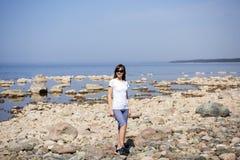 Portret van het glimlachen het jonge vrouw leggen op overzeese kust stock foto