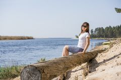 Portret van het glimlachen het jonge vrouw leggen op overzeese kust stock afbeelding