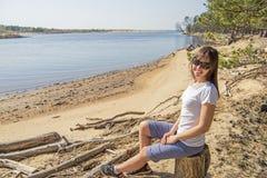 Portret van het glimlachen het jonge vrouw leggen op overzeese kust stock foto's