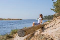 Portret van het glimlachen het jonge vrouw leggen op overzeese kust royalty-vrije stock afbeelding