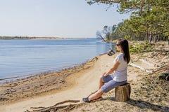 Portret van het glimlachen het jonge vrouw leggen op overzeese kust royalty-vrije stock afbeeldingen