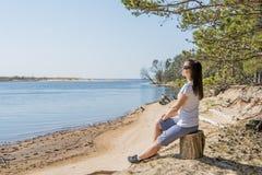 Portret van het glimlachen het jonge vrouw leggen op overzeese kust royalty-vrije stock foto's