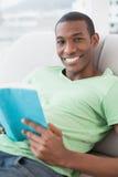 Portret van het glimlachen van Afro-het boek van de mensenlezing op bank Stock Fotografie