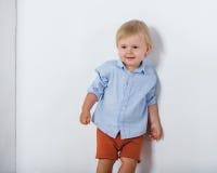 Portret van het glimlachen van leuk weinig jongen dichtbij witte muur Stock Foto's