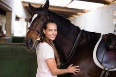 Portret van het glimlachen van vrouwelijke jockey die zich door paard bevinden royalty-vrije stock afbeelding