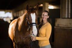 Portret van het glimlachen van vrouwelijke jockey die zich door paard bevinden stock fotografie