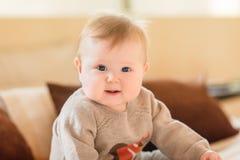Portret van het glimlachen van weinig kind met blond haar en blauwe ogen die gebreide sweaterzitting op bank dragen en camera bek royalty-vrije stock fotografie