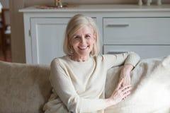 Portret van het glimlachen het verouderde vrouw ontspannen op comfortabele laag stock foto's