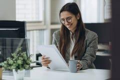 Portret van het glimlachen van vrij jonge bedrijfsvrouw in glazen die op werkplaats zitten en met documenten werken stock fotografie