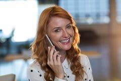 Portret van het glimlachen vrouw het spreken op telefoon in bureau Royalty-vrije Stock Afbeeldingen