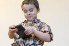 Portret van het glimlachen weinig jongen die mobiele die telefoon houden over lichte achtergrond wordt ge?soleerd leuke jong geit royalty-vrije stock afbeelding