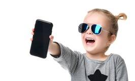 Portret van het glimlachen weinig mooi meisje die het lege scherm mobiele telefoon in blauwe zonnebril tonen Stock Foto