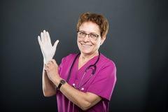 Portret van het hogere dame arts zetten op steriele handschoenen royalty-vrije stock afbeelding