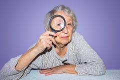 Portret van het hogere vrouw kijken door een vergrootglas over lilac achtergrond Royalty-vrije Stock Foto