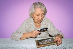 Portret van het hogere vrouw kijken door een vergrootglas over lilac achtergrond Royalty-vrije Stock Afbeelding