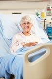 Portret van het Hogere Vrouwelijke Geduldige Ontspannen in het Bed van het Ziekenhuis Stock Foto