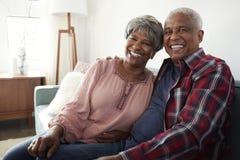 Portret van het Houden van het Hogere Paar Ontspannen op Sofa At Home royalty-vrije stock afbeeldingen