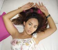 Portret van het jonge aantrekkelijke en mooie Aziatische vrouw liggen op bed bij slaapkamer die het sexy kijken stellen aan de ca royalty-vrije stock afbeeldingen