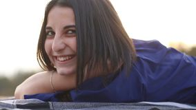 Portret van het jonge donkerbruine gelukkige mooie vrouw in openlucht liggen stock footage