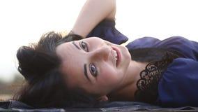 Portret van het jonge donkerbruine gelukkige mooie vrouw in openlucht liggen stock video
