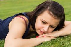 Portret van het jonge donkerbruine meisje liggen op een gras Royalty-vrije Stock Afbeeldingen