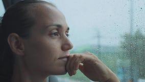 Portret van het jonge droevige vrouw kijken uit het natte venster, terwijl het reizen door bus stock videobeelden