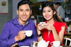 Portret van het jonge en gelukkige Aziatische paar ontspannen samen in koffiewinkel royalty-vrije stock afbeelding