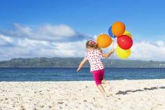 Portret van het jonge gelukkige meisje lopen door zandstrand op Se Royalty-vrije Stock Foto