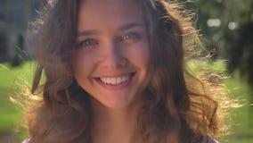 Portret van het jonge glimlachen, het lachen Kaukasisch brunette in het park, universiteit op de achtergrond stock video