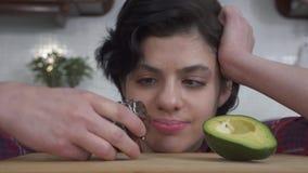 Portret van het jonge hongerige meisje kiezen tussen verse avocado en smakelijke browniecake en na het eten van cake Sluit omhoog stock videobeelden
