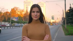 Portret van het jonge Kaukasische donkerbruine letten op in camera met bescheiden die glimlach en wapens op wegachtergrond worden stock footage