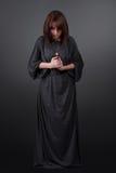 Portret van het jonge Kaukasische vrouw bidden Het gebedmeisje kleedde zich in Gewaden van een non op grijze studioachtergrond Stock Foto's