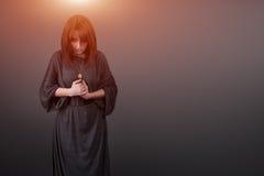 Portret van het jonge Kaukasische vrouw bidden Het gebedmeisje kleedde zich in Gewaden van een non op grijze studioachtergrond Stock Afbeelding