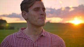 Portret van het jonge knappe mens hoofd draaien en het bekijken camera, het glimlachen, mooi groen gebied met binnen zonsondergan stock footage