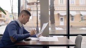 Portret van het jonge mannelijke architect werken in koffie dichtbij het venster en weg het werpen van documenten stock videobeelden