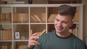 Portret van het jonge mannelijke student dansen aan de muziek die koel en ontspant bij bibliotheek zijn die stock footage