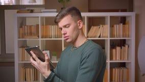 Portret van het jonge mannelijke student letten aandachtig op in tablet die aandachtig en geinteresseerd bij bibliotheek is stock video
