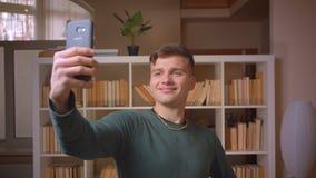 Portret van het jonge mannelijke student maken selfies op smartphone die positief en blij bij bibliotheek zijn stock videobeelden