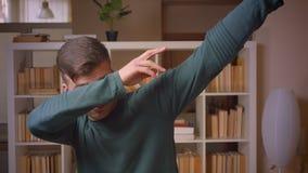 Portret van het jonge mannelijke student synchroniseren die succes hebben bereikt bij bibliotheek stock videobeelden